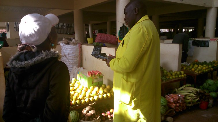 City  council attendant using the POS system to collect market revenue